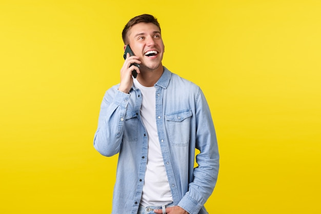 Technology, lifestyle concept. joyful handsome smiling man having happy conversation on phone, calling friend, looking enthusiastic up and holding smartphone near ear, yellow background.