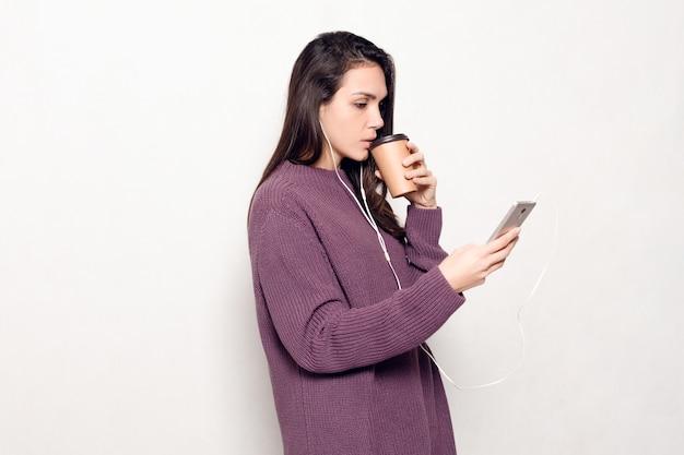 テクノロジー、ライフスタイル、インターネット中毒、人々のコンセプト-スマートフォンを持つ若い美しい女性。携帯電話を見て幸せで笑顔の魅力的な女性。背景の灰色の壁。
