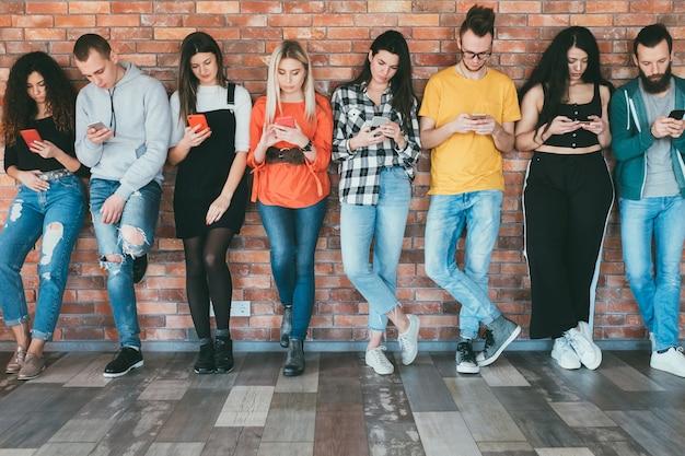 Технологический образ жизни. зависимость от социальных сетей. миллениалы со смартфонами в руках.