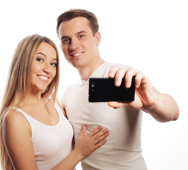 Концепция технологии, любви и дружбы - улыбающаяся пара со смартфоном, селфи и веселье. студия выстрелил на белом фоне.