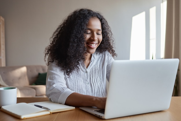Technology, occupation, freelance and networking concept. charming young dark skinned female marketing expert working distantly from home office, typing on laptop, making notes and havning coffee