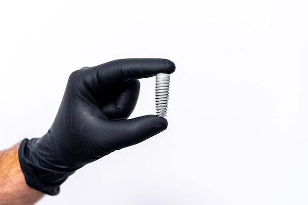 歯科医の手で白く分離された歯のインプラントの技術。黒のラテックス手袋。