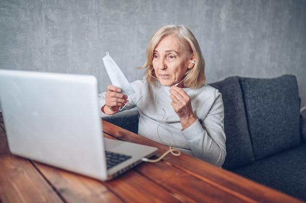 技術、老後、人々の概念-コロナウイルスcovid19パンデミック中に自宅でラップトップコンピューターを使用して作業し、自宅のラップトップコンピューターでビデオ通話を行う顔医療マスクを持つ年配の年配の女性。ホームステイのコンセプト