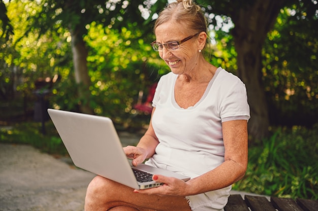 Technology, old age people concept - elderly happy senior old woman working online with laptop computer outdoor in the garden. remote work, distance education.