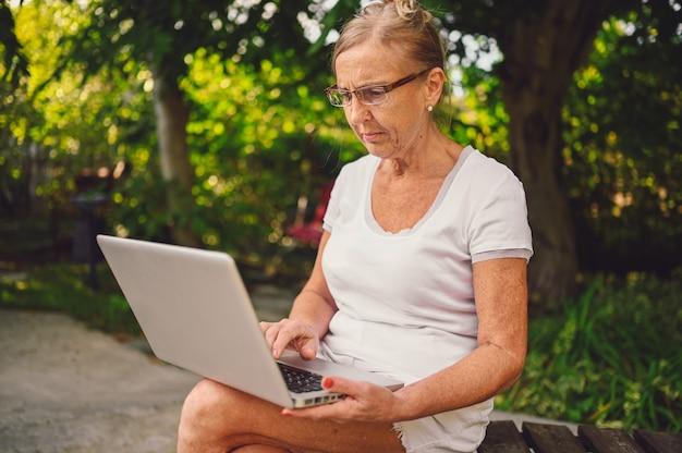 기술, 노년 사람들이 개념-정원에서 야외 노트북 컴퓨터와 온라인으로 작업 노인 행복 수석 늙은 여자. 원격 근무, 원격 교육.