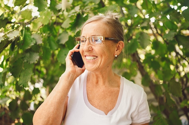 Technology, old age people concept - elderly senior old happy smiling woman in prescription eyeglasses speaks smartphone outdoor in the garden.