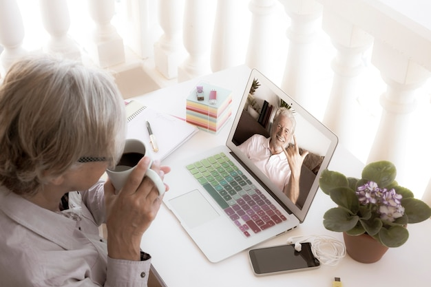 Technology and older people. gray-haired senior woman outdoors in the terrace using laptop for video calling with her smiling husband. retired couple using new technologies
