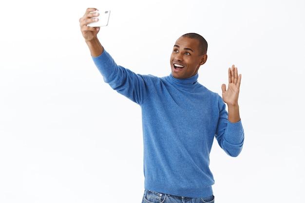 テクノロジー、オンラインライフスタイルのコンセプト。フレンドリーなアフリカ系アメリカ人の男性が、こんにちはと言って、ビデオコールします