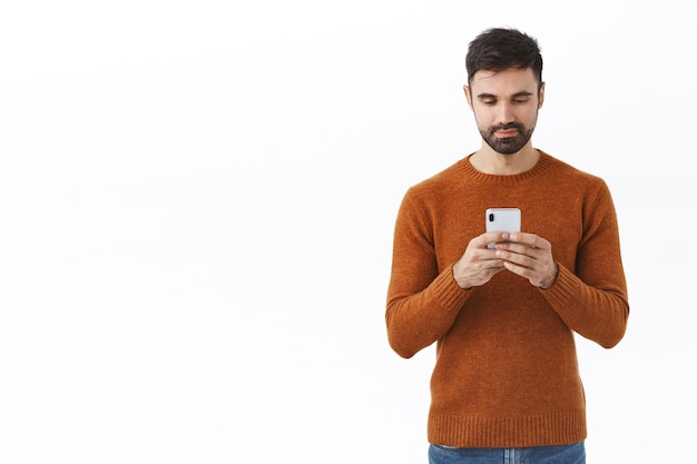 Technology, online lifestyle and people concept. portrait of handsome businessman with beard, contact business partner via message, texting friend, holding mobile phone, looking at smartphone