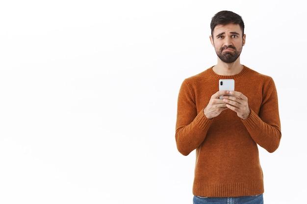 テクノロジー、人、コミュニケーションのコンセプト。不幸な、あごひげを生やして、顔をゆがめ、悲しそうにしかめっ面の暗い男の肖像画、不幸な携帯電話を持って、動揺のメッセージを受信します