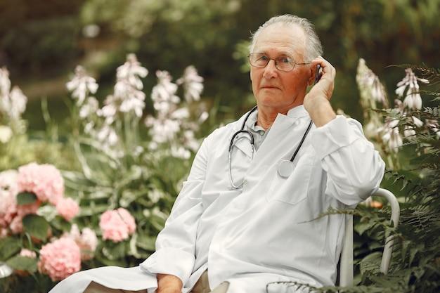 テクノロジー、人、コミュニケーションのコンセプト。サマーパークの年配の男性。電話を使っている医者。