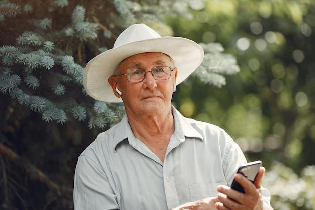 テクノロジー、人、コミュニケーションのコンセプト。サマーパークの年配の男性。電話を使用しているgrangfather。
