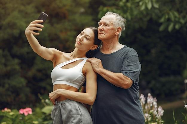 기술, 사람 및 통신 개념. 여름 공원에서 수석 남자입니다. 손녀와 Grangfather. 무료 사진