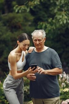 기술, 사람 및 통신 개념. 여름 공원에서 수석 남자입니다. 손녀와 grangfather.