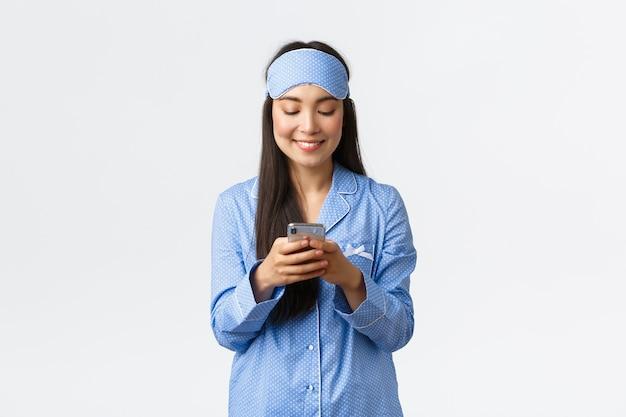 Технологии, люди и концепция домашнего досуга. улыбающаяся милая азиатская женщина-блогер в пижаме и спальной маске, пишет пост в социальных сетях перед сном, обменивается сообщениями с мобильным телефоном