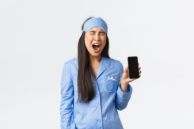 テクノロジー、人、ホームレジャーのコンセプト。疲れて悩むかわいいアジアの女の子が電話で目覚めたと不平を言い、眠っているマスクとパジャマに悩まされて叫び、モバイル画面を見せています。
