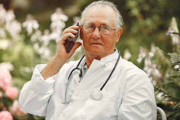 Tecnologia, persone e concetto di comunicazione. uomo maggiore al parco estivo. medico che utilizza un telefono.