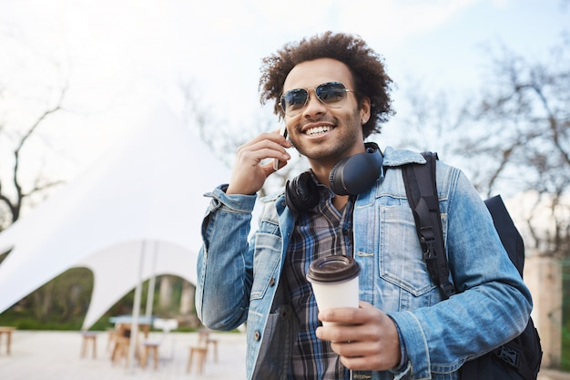 Technology and people concept. young handsome dark-skinned male with bristle and afro haircut talking on cellphone while drinking coffee and walking around city, wearing backpack and denim coat.