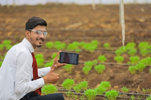 Technology and people concept, young indian agronomist using tablet or smartphone at greenhouse