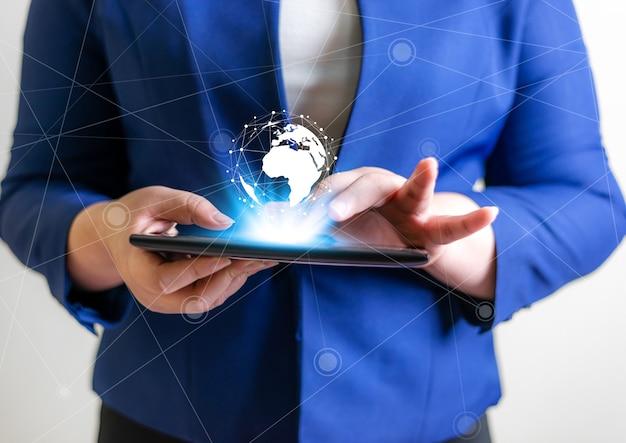 技術者のグローバル接続ネットワークの概念、ラップトップと仮想地球のぼやけた背景を持つビジネスの女性
