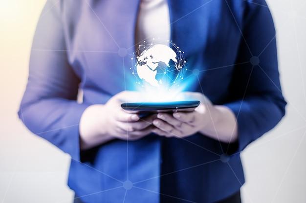 テクノロジーの人々のグローバル接続ネットワークの概念、ラップトップと仮想地球を持つビジネスウーマン