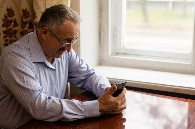 Технологии, люди, образ жизни и концепция коммуникации - счастливый старший мужчина набирает номер телефона и отправляет текстовые сообщения на смартфоне дома