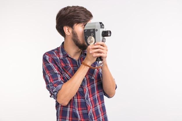 技術、写真、人々の概念-コピースペースと白い背景の上のビンテージカメラで写真を撮る格子縞のシャツのハンサムな男
