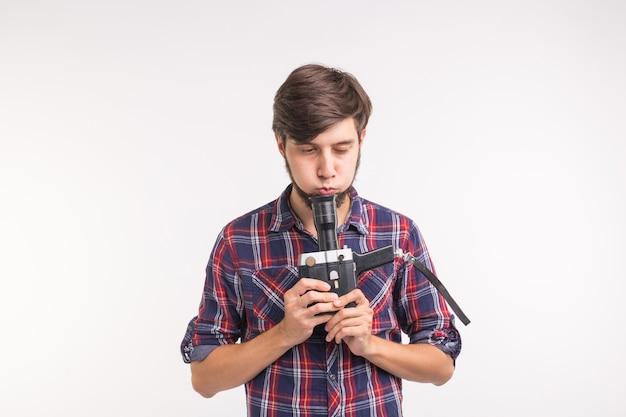 Концепция технологии, фотографии и людей - красивый мужчина в клетчатой рубашке фотографирует на винтаж