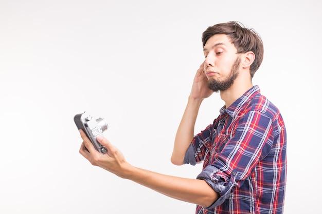 Концепция технологии, фотографии и людей - красивый мужчина в клетчатой рубашке, делающий селфи на старинную камеру.