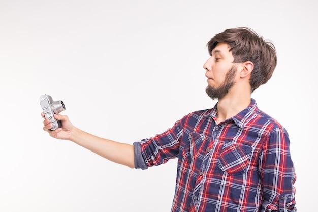 Технологии, фотография и люди концепции - красивый мужчина в клетчатой рубашке, делающий селфи на винтаж