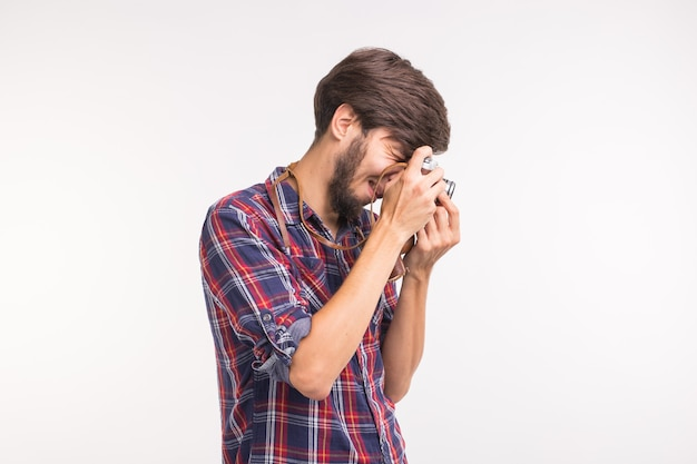 Technology, photography and people concept - handsome man in plaid shirt taking a photo on retro camera. Premium Photo