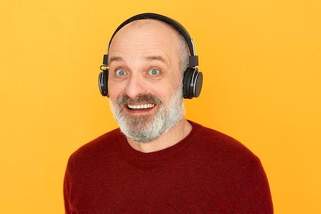 テクノロジー、リラクゼーション、そして高齢者。ヘッドフォンを使用してラジオでスポーツの生放送を聞いている、はげ頭と灰色のひげを持つ幸せな魅力的な老人は、エネルギッシュな興奮した表情をしています