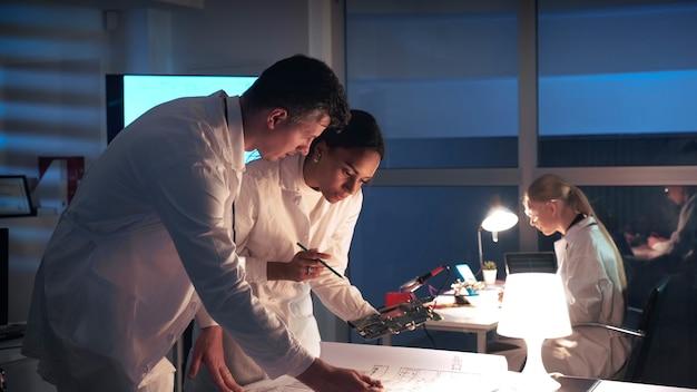 Лаборатория технологических исследований инженеров-электронщиков смешанной расы в белых халатах, работающих с электронной платой и схемой управляющей электроники в лаборатории