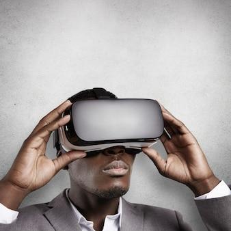 技術、科学、革新、サイバースペースのコンセプト。オフィスでゴーグルを着ている若い浅黒い肌の従業員の肖像画。