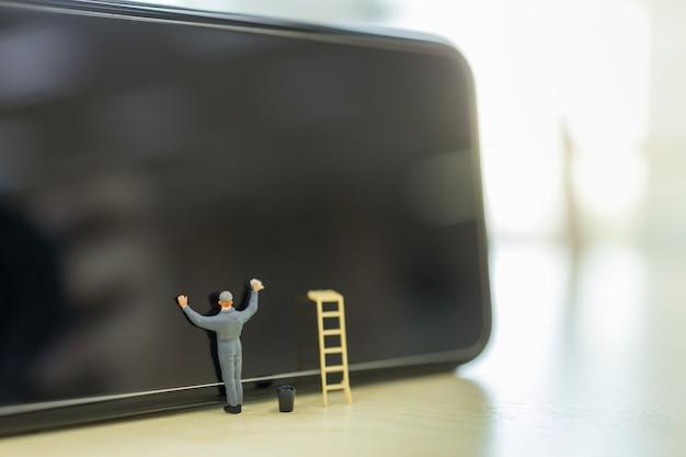 기술, 보안 및 정화 개념. 양동이와 사다리 스마트 휴대 전화의 작업자 미니어처 그림 사람들이 서, 닦아 및 깨끗 한 화면 닫습니다.