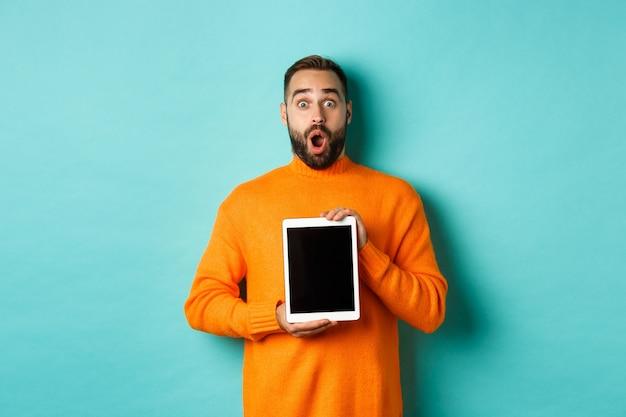 Tecnologia. mascella di caduta dell'uomo barbuto sorpreso, che mostra lo schermo della tavoletta digitale