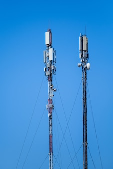 Technology of telecommunication gsm 5g,4g,3g tower. cellular phone antennas on a building roof. receiving and transmitting stations with blue skies on the background.