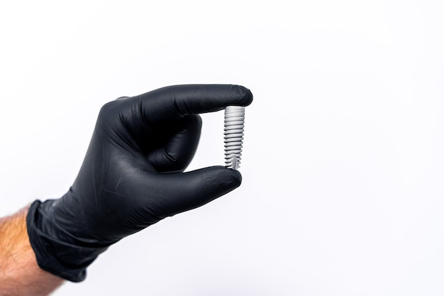 Technology of tooth implants isolated on white in dentist s hand. black latex gloves.