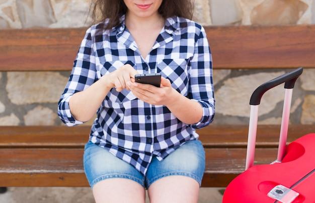 テクノロジー、旅行、人々のコンセプト-ベンチに座って電話で入力する若い女性のクローズアップ。