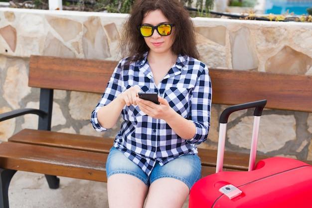 기술, 여행 및 사람들 개념-젊은 여자는 맑은 안경에 벤치에 앉아 전화에 입력합니다.