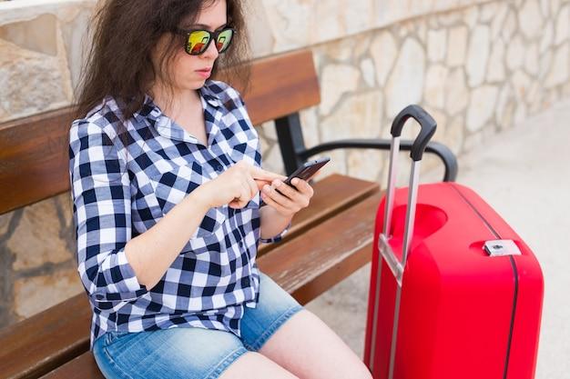 기술, 여행 및 사람 개념입니다. 젊은 여자는 맑은 안경에 벤치에 앉아서 전화를 입력합니다.