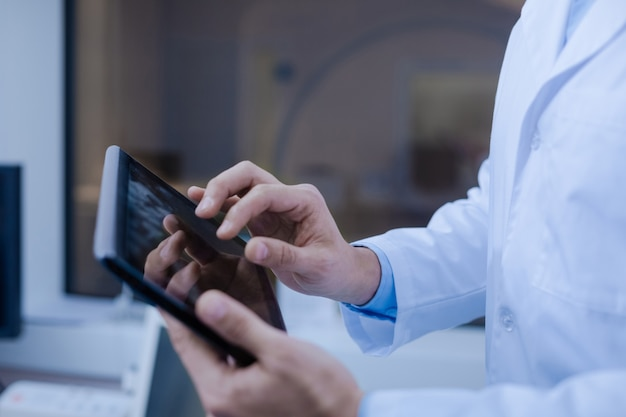 Technology in use. close up of a modern innovative tablet being in the doctors hands while being used for work