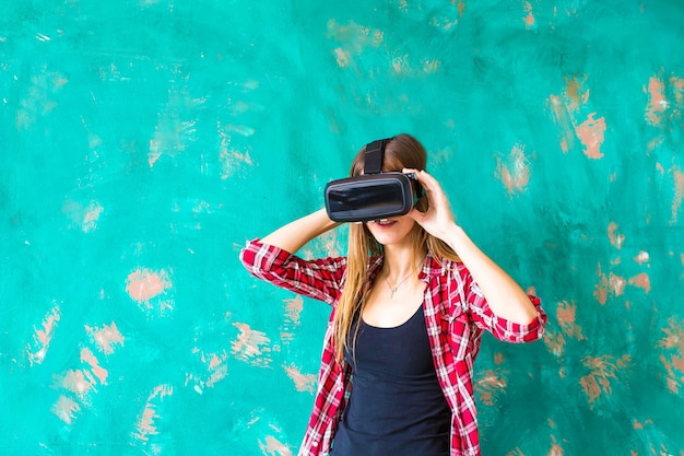 기술, 가상 현실, 엔터테인먼트 및 사람 개념. 회색 배경 위에 가상 현실 헤드셋 또는 3d 안경과 헤드폰을 가진 행복한 젊은 여성