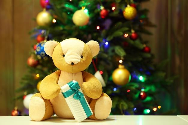 クリスマスツリーの背景にテディベアとギフトボックス