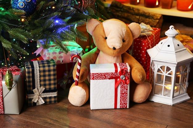 Плюшевый мишка и подарочные коробки возле елки, крупным планом