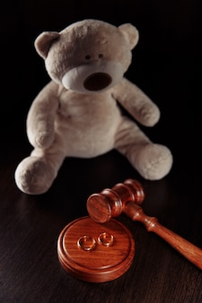 Teddy bear as a symbol of childrens protection and rings on a wooden table