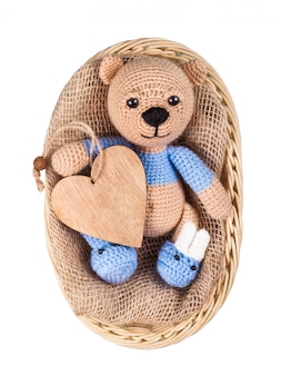 Teddy bear in basket and wooden heart