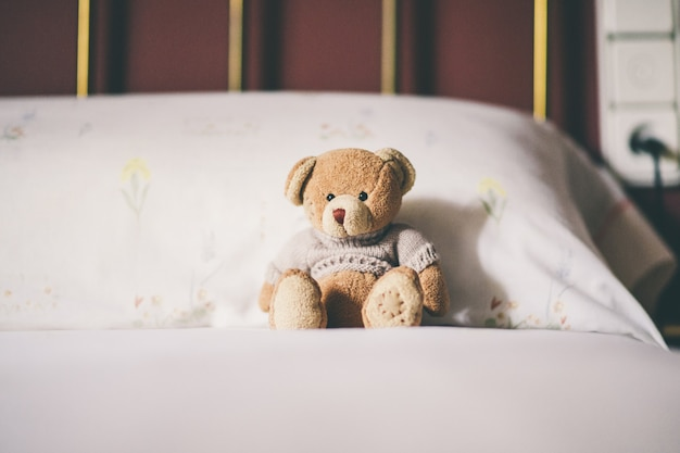 Teddy bear on the bed, space for text.