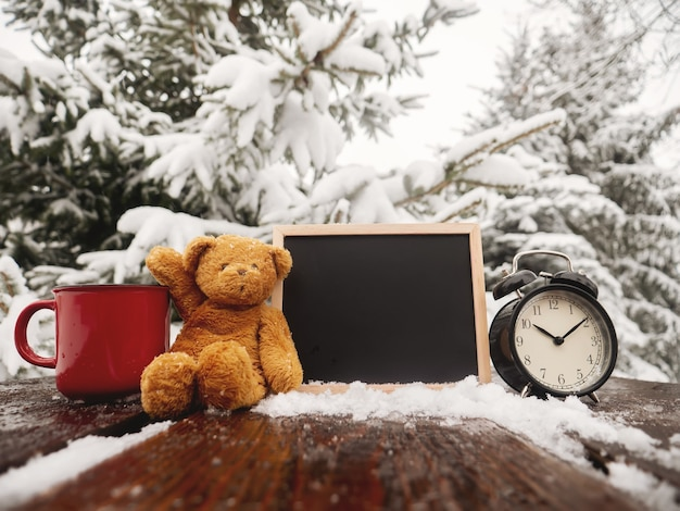 Teddy bear and blackboard with alarm clock on wooden table in blizzard