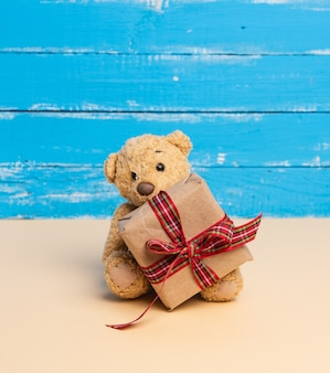 Teddy bear and blue square cardboard box with red bow on a blue wooden